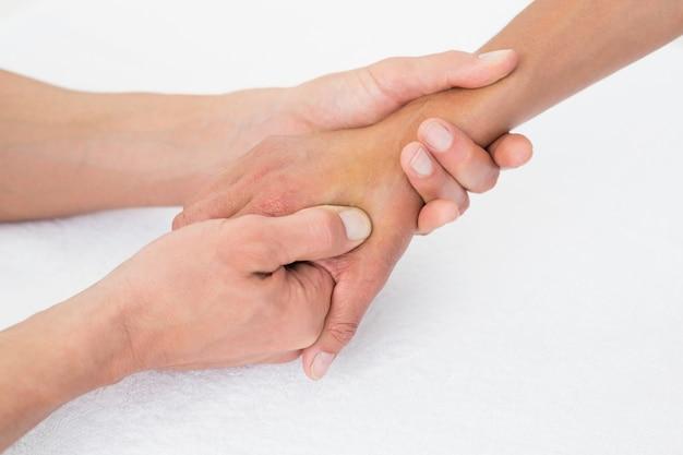 Doktor, der eine weibliche patientenhand überprüft
