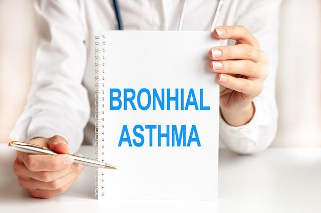 Doktor, der eine weiße karte in den händen hält und das wort bronhial asthma zeigt. konzeption des gesundheitswesens für krankenhäuser, kliniken und medizinische unternehmen.
