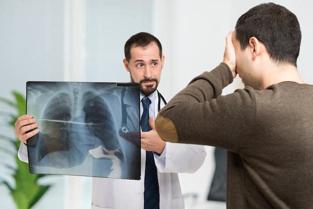 Doktor, der einem verzweifelten patienten radiographie zeigt