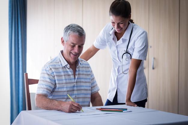 Doktor, der einen älteren mann beim zeichnen in zeichnungsbuch unterstützt