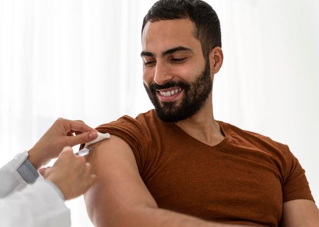 Doktor, der einen gutaussehenden smiley-mann impft