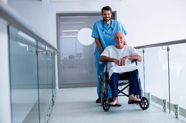Doktor, der einen patienten auf rollstuhl schiebt