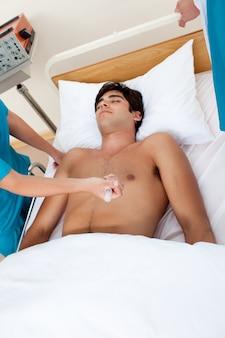 Doktor, der einen patienten mit einer einspritzung des adrenalin wiederbelebt