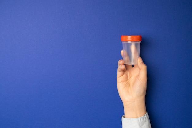 Doktor, der einen plastikbehälter mit samenzellen für medizinische analyse hält.