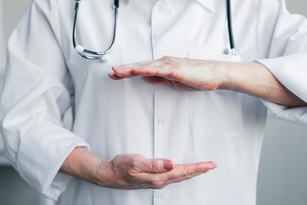 Doktor, der einen raum mit den händen darstellt