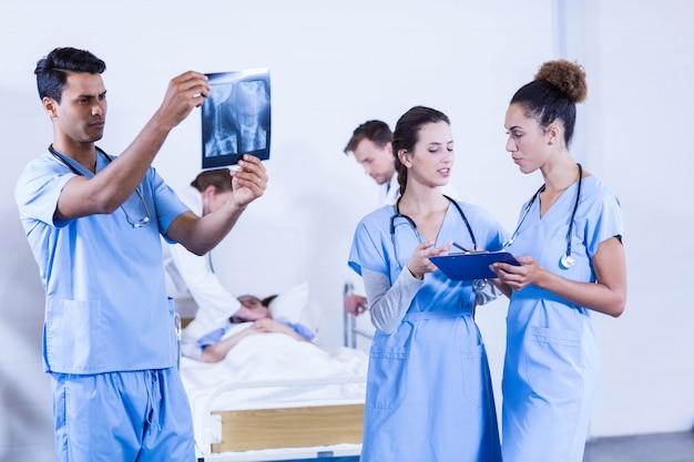 Doktor, der einen röntgenstrahl im krankenhaus und in seinen kollegen haben eine diskussion überprüft