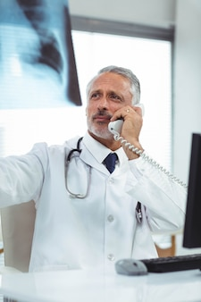 Doktor, der einen röntgenstrahlbericht bei der unterhaltung am telefon an der klinik überprüft
