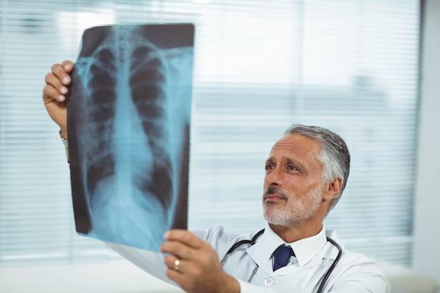 Doktor, der einen röntgenstrahlbericht in der klinik überprüft