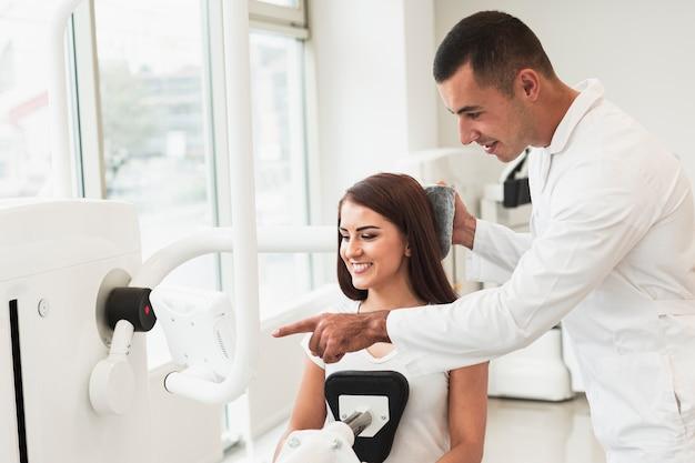 Doktor, der geduld zeigt, wie man ein gerät benutzt