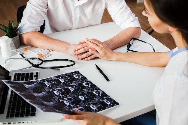 Doktor, der geduldige hand und eine radiographie hält