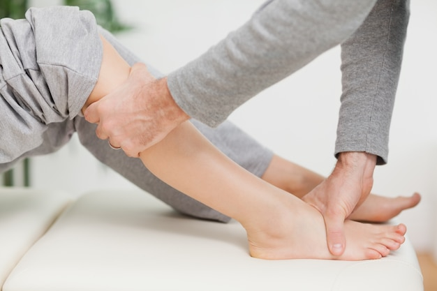 Doktor, der gelenkmobilisierung mit dem knie eines patienten macht