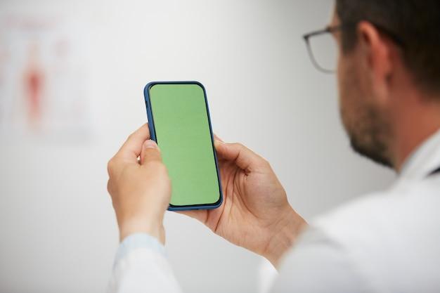 Doktor, der green-screen-smartphone hält, leitender arzt, der chroma-key-telefon im medizinischen schrank im weißen kleid und in den gasen sitzt