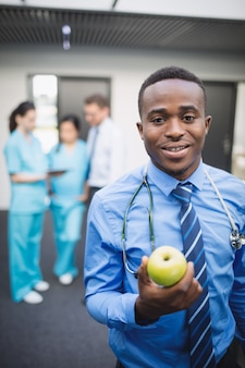 Doktor, der grünen apfel im krankenhauskorridor hält