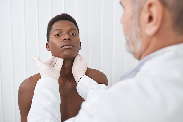 Doktor, der hals des afrikanischen patienten tastet.