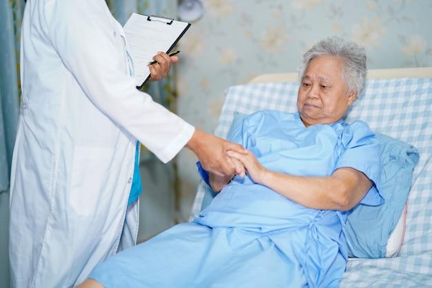 Doktor, der hand mit asiatischem älterem frauenpatienten hält.