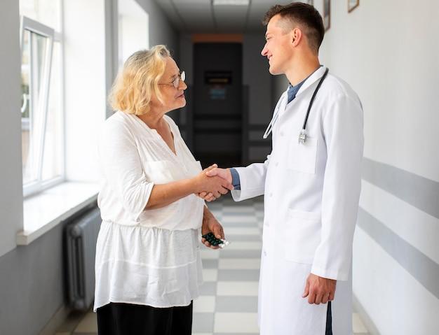 Doktor, der hand mit patienten rüttelt