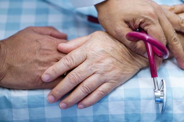 Doktor, der handasiatischen älteren frauenpatienten mit liebe berührt.