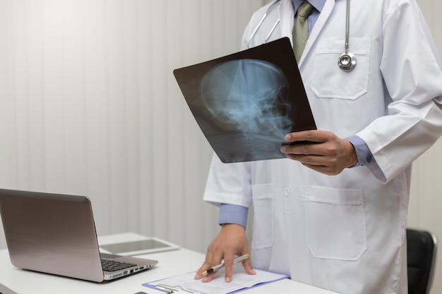 Doktor, der hauptröntgenstrahl im büro schaut.