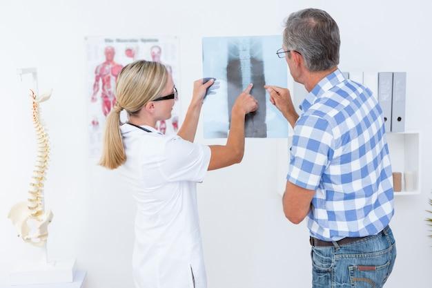 Doktor, der ihrem patienten röntgenstrahlen zeigt