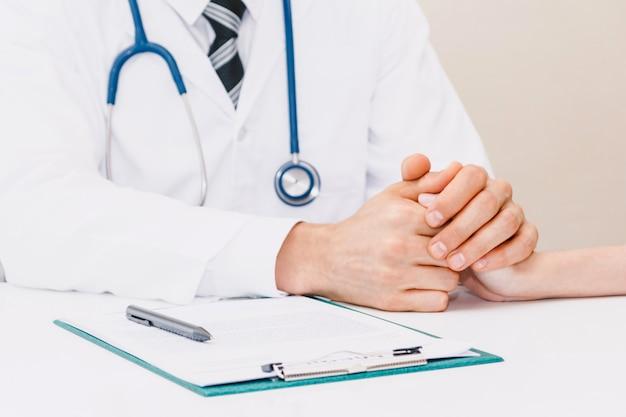 Doktor, der ihren weiblichen patienten sorgfältig auf doktortabelle im krankenhaus versichert. gesundheitswesen und medizin
