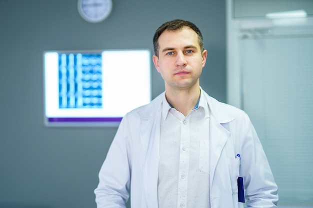 Doktor, der im büro mit röntgenstrahl auf dem hintergrund steht.