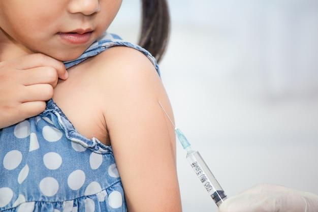 Doktor, der impfung im arm des asiatischen kindes des kleinen kindes, gesundes und medizinisches konzept einspritzt