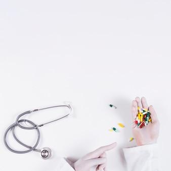 Doktor, der in der hand auf bunte kapseln mit stethoskop auf weißem hintergrund zeigt