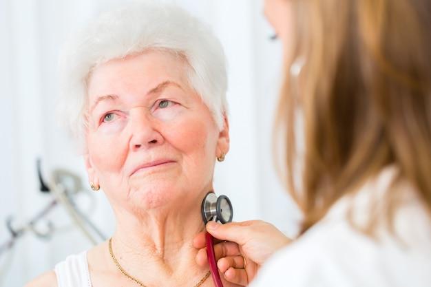 Doktor, der in der praxis älteren patienten auskultiert