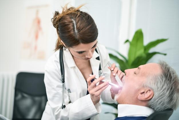 Doktor, der in einem patientenmund schaut