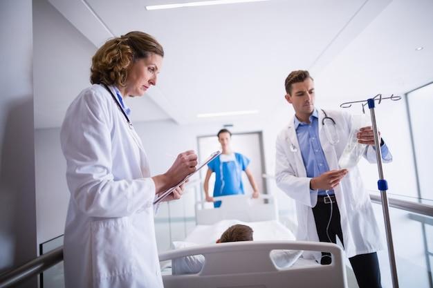 Doktor, der iv tropf einstellt, während patient auf bett liegt