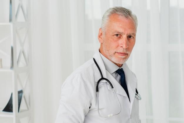 Doktor, der kamera betrachtend steht