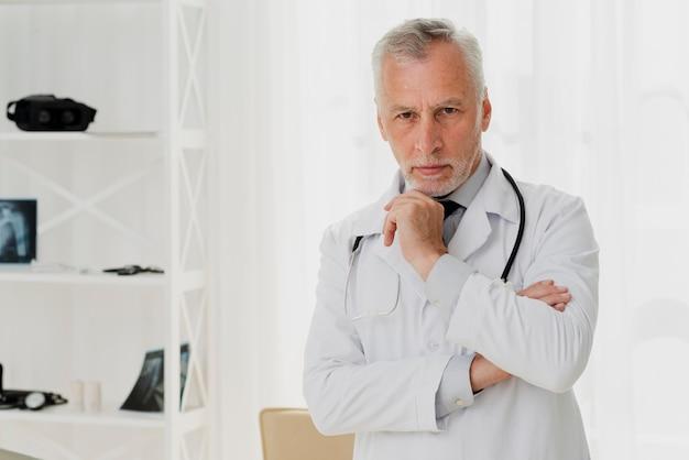 Doktor, der kamera mit der hand auf kinn betrachtet