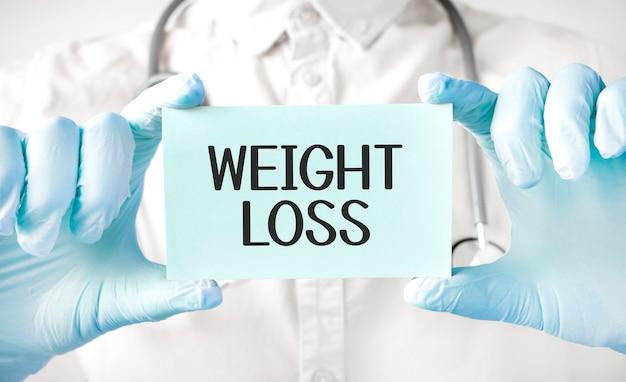 Doktor, der karte in händen hält und das wort gewichtsverlust zeigt
