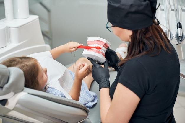 Doktor, der kleinem patienten zeigt, wie man zähne putzt.