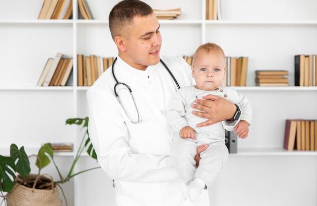 Doktor, der kleines baby hält und ihn betrachtet