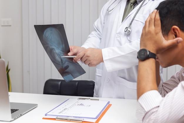 Doktor, der kopfröntgenstrahlfilm schaut und erklärt den patienten symptome und medizinische behandlung
