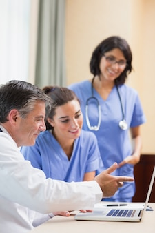 Doktor, der krankenschwestern etwas auf laptop zeigt