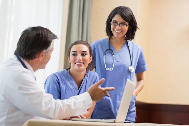 Doktor, der lächelndes krankenschwestern etwas auf laptop zeigt