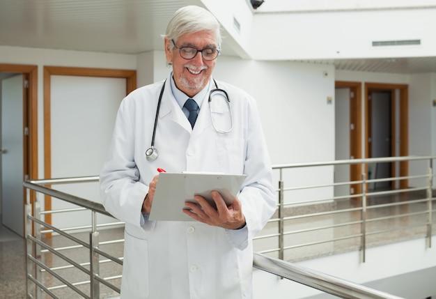 Doktor, der lächelt, wie betrachtet patientenakte