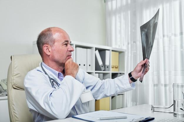 Doktor, der lungenröntgen betrachtet