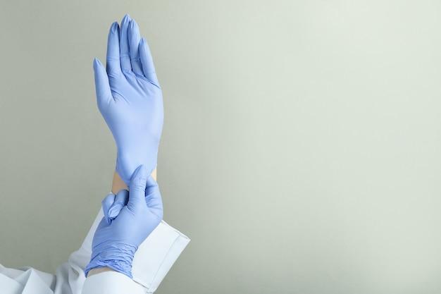 Doktor, der medizinische handschuhe auf hellgrau anzieht