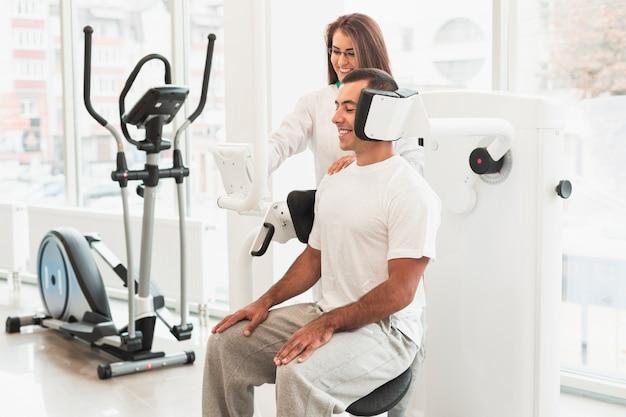 Doktor, der medizinisches gerät auf männlichen patienten justiert