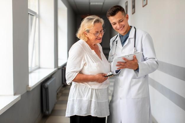 Doktor, der mit älterem patienten spricht