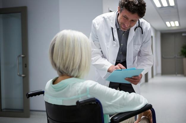 Doktor, der mit dem patienten interagiert, der auf rollstuhl im korridor sitzt