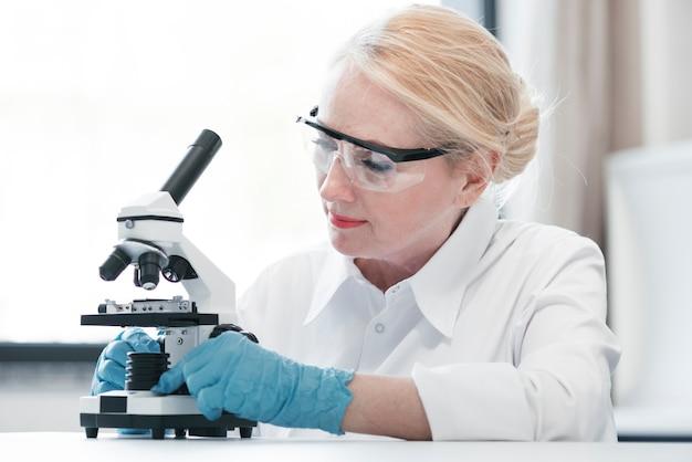 Doktor, der mit einem mikroskop analysiert