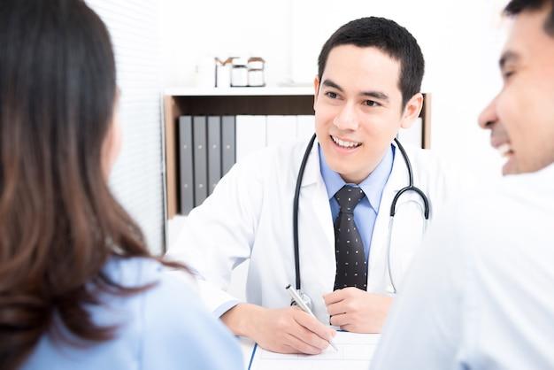 Doktor, der mit jungen paarpatienten sich berät