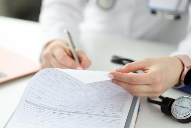 Doktor, der mit kugelschreiber in patientenanamnese nahaufnahme schreibt. pflege des krankenaktenkonzepts