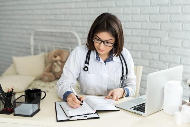Doktor, der mit laptop arbeitet und auf papierkram schreibt. krankenhaushintergrund.
