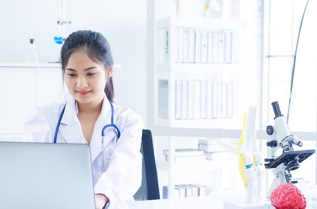 Doktor, der mit laptop-computer arbeitet und auf schreibarbeit schreibt. krankenhaus hintergrund