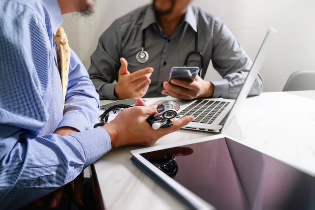 Doktor, der mit moderner digitaler tablettenlaptop-computer des intelligenten telefons arbeitet